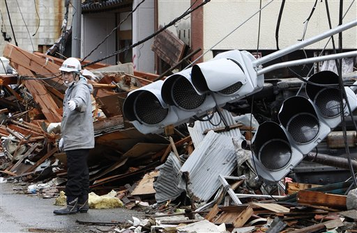A construction laborer controls the traffic at a devastated area in Kesennuma, Miyagi Prefecture Wednesday.