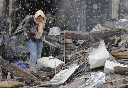 Braving falling snow, a woman looks around destroyed factory in the rubble Wednesday in Miyagi Prefecture.