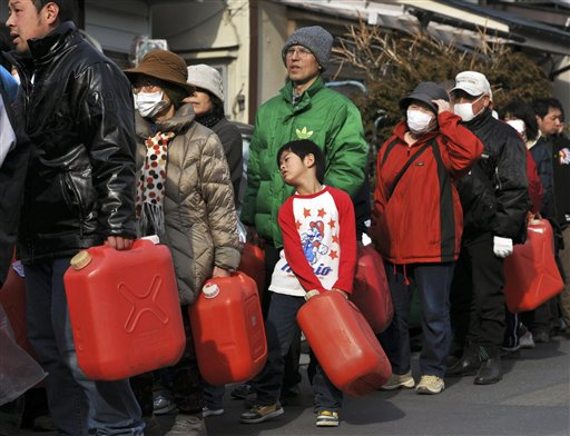 A boy waits in a line in front of a gas station in Kamaishi, northern Japan Monday.