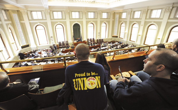 Marc Love, left, and Lance Hackett, right, both of Wells and both members of the United Food Commercial Workers Union Local 791 watch activity in the Maine Legislature from the house gallery on Tuesday, March 22, 2011. The pair was part of the 300 or so union workers that gathered to lobby their prospective house representatives to defeat  LD 309 and LD 788.