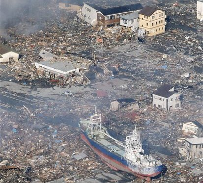 A large ship sits among rubble after it was swept by a tsunami to the city center of Kesennuma, northeastern Japan, on Saturday March 12, 2011, one day after a giant quake and tsunami struck the country's northeastern coast.