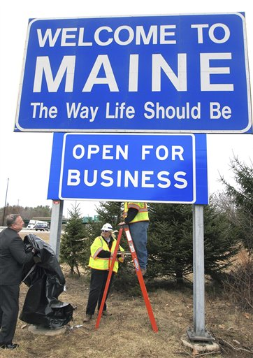 Maine Gov. Paul LePage, left, unveils a new &quotOpen for Business&quot sign beneath the &quotWelcome to Maine&quot sign along Interstate 95 near the New Hampshire border in Kittery, Maine, Friday, March 18, 2011. Maine Department of Transportation crew supervisors Elaine Cota, center, and Aaron Main, on ladder, assisted. The ceremonial event helped fulfill LePage's campaign promise to bring jobs to the state.