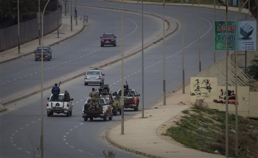Libyan rebels drive through the deserted city of Benghazi after a plane of Gadhafi's forces was shot down over , eastern Libya, Saturday.