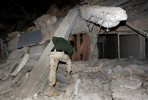 A Libyan soldier surveys the damage to an administrative building hit by a missile late Sunday, March 20, 2011 in the heart of Moammar Gadhafi's Bab Al Azizia compound in Tripoli, Libya.