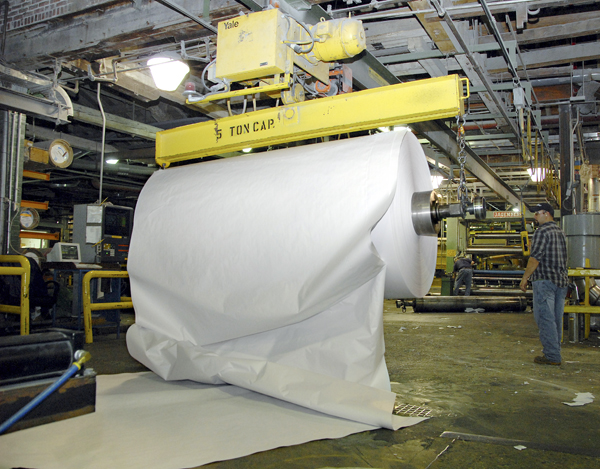 A large roll of freshly-made paper gets pulled from a papermaking machine at Lincoln Paper and Tissue LLC on Friday.