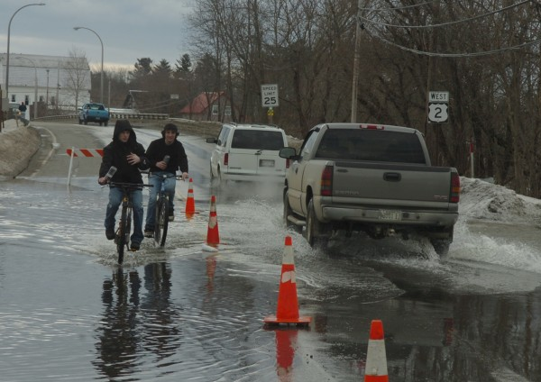 Andrew Tash (left) of Chester and David Fogg of Mattawamkeag ride their bikes through flooded Route 2 on Sunday.