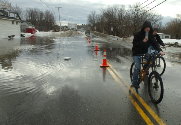 Andrew Tash (left) of Chester, and David Fogg of Mattawamkeag ride their bikes through flooded Route 2 on Sunday, March 13, 2011.