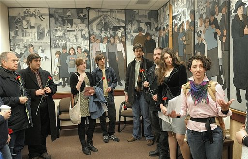 In this March 25, 2011 photo, Jessica Graham, right, of Waterville, Maine, leads a gathering in front of a mural honoring labor, in the Department of Labor building's lobby in Augusta, Maine. The group gathered to honor the 100th anniversary of the New York Triangle Shirtwaist Factory fire, which killed 146 garment workers. The mural was taken down over the weekend after Gov. Paul LePage ordered it removed.