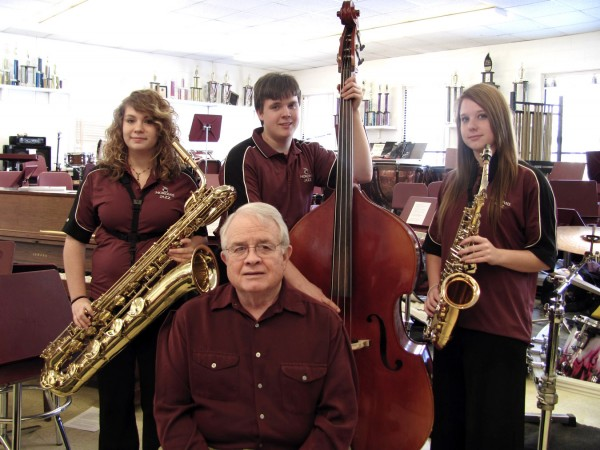 Stanley Buchanan, seated, has been a music teacher in the Newport area for 46 years, since before the existence of Nokomis Regional High School. Buchanan, who is with groups of student musicians today at the Berklee High School Jazz Festival. Above, Buchanan poses with the Nokomis Jazz Ensemble's seniors on Friday. From left, students are Britany Seale of Pittsfield, Tyler Jones of Newport and Katie Webber of Etna.
