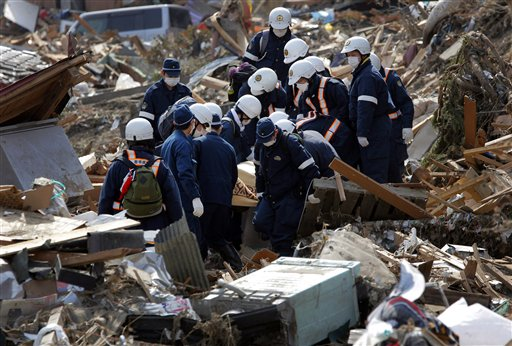 Police officers carry the body of a victim in Rikuzentakata, Iwate Prefecture, northern Japan, Monday.