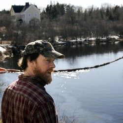 Dwayne Shaw, executive director of the Pleasant River Fish Hatchery in Columbia Falls surveyed the oil sheen drifting down the Pleasant River on Tuesday, just upstream from his hatchery research facility. The Maine Dept. of Environmental Protection, the Maine Dept. of Marine Resources and Clean Harbor Environmental Services quickly responded to the oil spill reported off the Tibbettstown Road in Columbia Falls. Behind him is a sorbent boom that the D.E.P installed to help collect the contaminant.