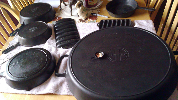 An assortment of frying pans in Loren Schuck's collection from a tine 2 inch pan to a nearly 2 foot-diameter pan.