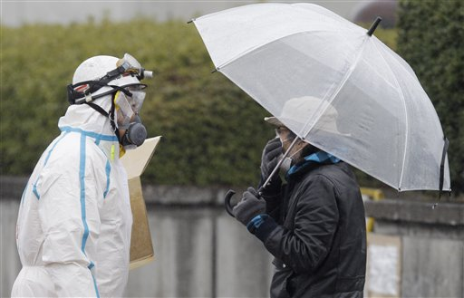 An official wearing a protective suit helps usher people through a radiation emergency scanning center in Koriyama, Japan, Tuesday, March 15, 2011, four days after a giant quake and tsunami struck the country's northeastern coast.