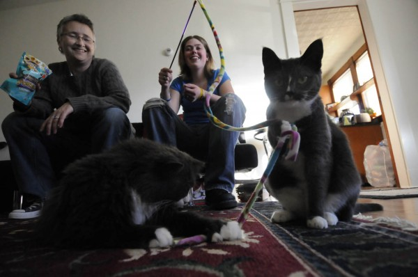 Christina Parrish (left) and her partner Meaghan Sulinski play with their cats Chenzi (from left) and Pip, at their home in Brewer Tuesday. Parrish, 43, was diagnosed with Stage 4 pancreatic cancer three years ago. Not happy with a grim prognosis, she looked for other treatment options in a search for a brighter future. She has been selected to be honorary chair for the 2011 Relay for Life of Penobscot.