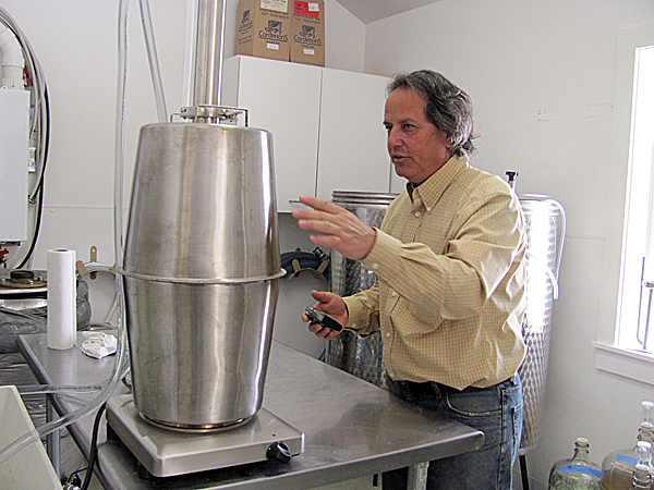 Steve Buchsbaum checks the temperature of a mini-still on Friday at the Tree Spirits Winery and Distillery. Buchsbaum was re-distilling the by-products of a previous batch done on a larger scale to experiment with ways to maximize purity and production.
