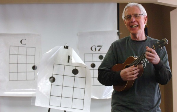 "Frets Halligan leads an ukulele on Saturday at the Newport Cultural Center in Newport.  After watching the documentary film ""Mighty Uke"", participants learned simple chords and played a few popular songs on the traditional Hawaiian instrument."