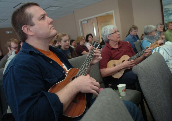 "Chris Healy (left) of Hampden and Jo Bennett (right) of Newport listen to some tips for ukulele playing on Saturday at the Newport Cultural Center in Newport. ""It sounds wonderful,"" Bennett said of the ukulele, which she first tried her hand at as a child."