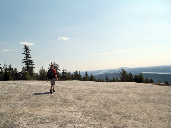 An unidentified hiker cross Great Pond Mountain, just one of several hiking trails provided by Great Pond Mountain Conservation Trust in Orland. Many of the over 100 land trusts in Maine contain hiking trails.
