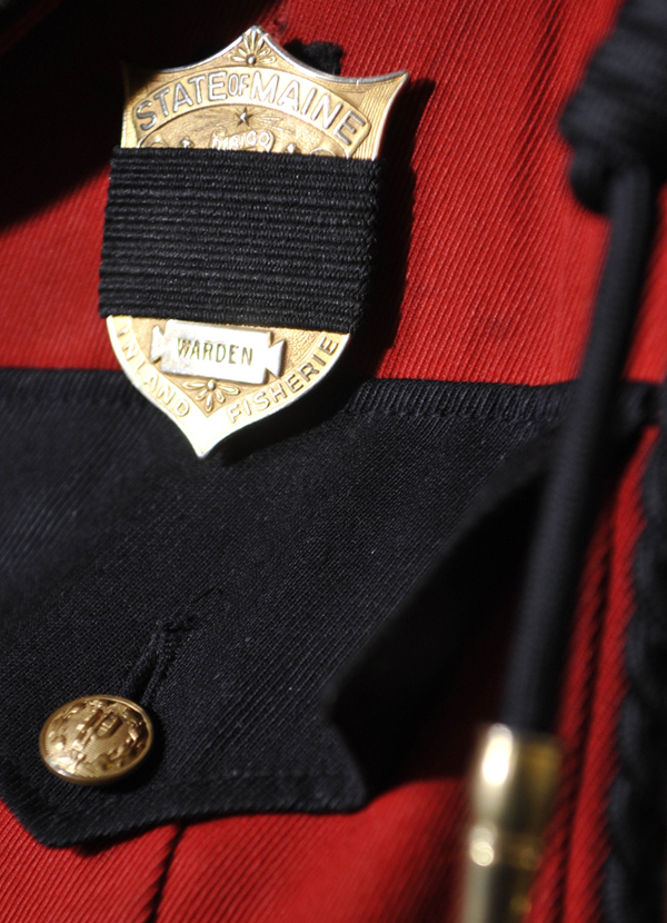 This warden's uniform wwas displayed with a black band over the badge at a press conference in Bangor as a tribute to fallen warden service personnel including warden Service Pilot Daryl Gordon.