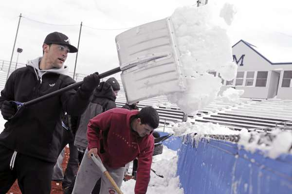 University of Maine outfielder Kyle Silva (left) helps teammates shovel snow from Mahaney Diamond Saturday morning, April 2, 2011. The baseball team's doubleheaders against Bryant University on Saturday and Sunday were cancelled due to the recent snowfall.