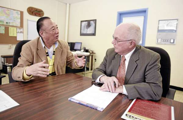 In this Wednesday, March 9, 2011 photo, Stearns High School superintendent Ken Smith, right, speaks with Tony Yu of the U.S. China Cultural Exchange Committee in Millinocket, Maine. Smith is recruiting foreign students in an effort to keep up the school's numbers and to avoid cuts in programs.