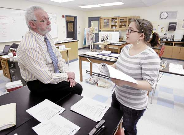 In this Thursday, March 10, 2011 photo, Stearns High School biology teacher Ken Wilkins, left, speaks with sophomore Stephanie Decker in Millinocket, Maine. The public high school is recruiting foreign students in an effort to keep up their numbers and to avoid cuts in programs.