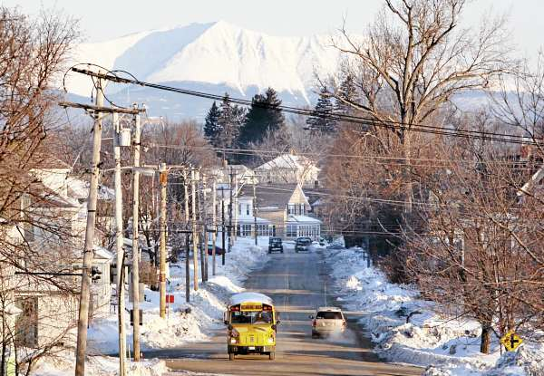 In this Wednesday, March 9, 2011 photo, Mount Katahdin rises in the background as a school bus makes its rounds in Millinocket, Maine. The town's public high school is touting its natural resources and it's proximity to Katahdin, in it's effort to recruit foreign students.
