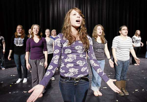 In this Thursday, March 10, 2011 photo, Mallory Osborne leads a song during show choir rehearsal at Stearns High School in Millinocket, Maine. The public high school is touting its successful performing arts program in it's efforts to recruit foreign students.