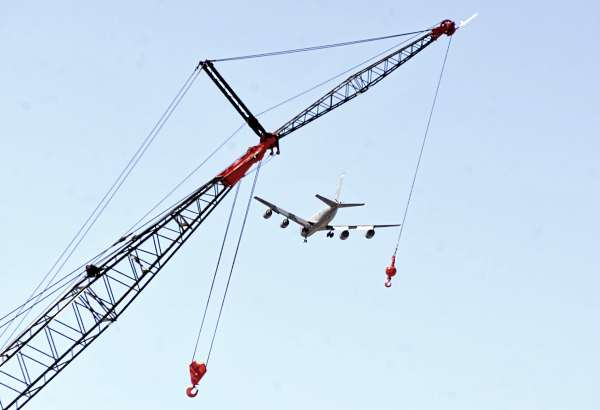 As it gets ready to land in Bangor, A KC-135E Stratotanker  appears to be lowered by a crane at Cianbro's Eastern Manufacturing Facility in Brewer Friday.