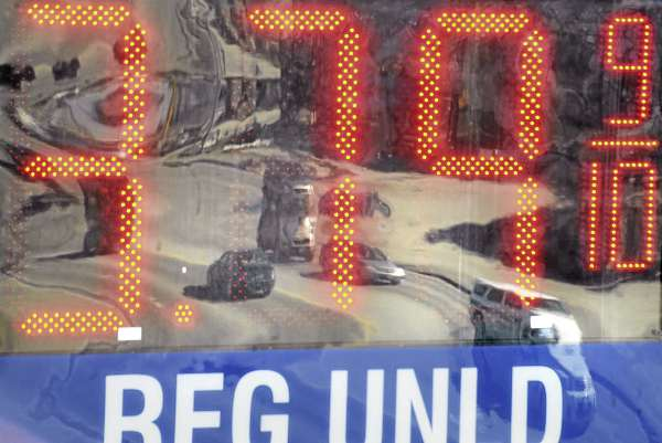 Passing cars are reflected in a gas station marquee on Broadway in Bangor.