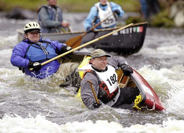 Cliff Raymond, left, of Gorham, Maine and Jim Minner, right, of Summerville, South Carolina dump their canoe at Six Mile Falls in Bangor during the Kenduskeag Stream Canoe Race on Saturday, April 17, 2010.