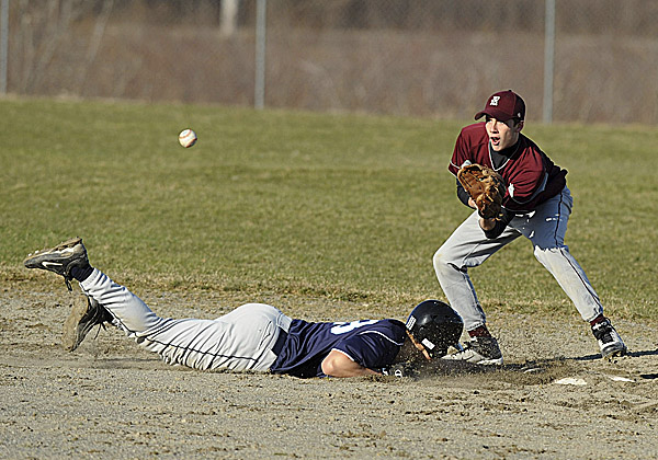 Lewis Francis of Calais High School dives back into second base during a pickoff attempt in the fourth inning of Friday's baseball season opener in East Machias against Washington Academy. WA's Alex Currier awaits the throw. Calais won 14-2.
