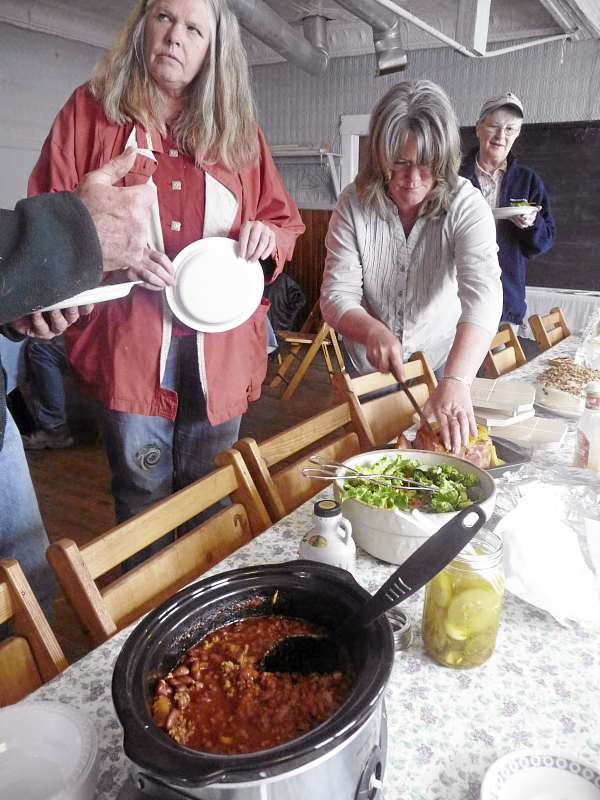 Farmers Karen Herrick of Robb Hill Farm in Alexander (left) and Terry Starks of Princeton serve up a community meal Sunday as plans are made for a Princeton Farmers' Market and a campaign to save the 1887 Princeton Grange. &quotThis is all about community and bringing people together,&quot Starks said.