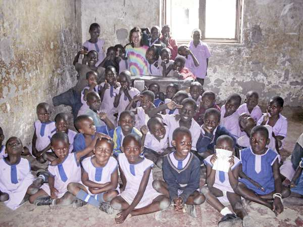 Dee Wilbur (rear) poses with school children in Uganda in 2009. Wilbur and Ben Brennan are organizing The Race for Human Race 5K road race set for May 1 at the University of Maine.