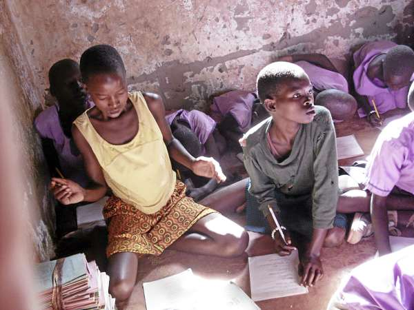 Students at a Ugandan orphanage do their work during a class while seated on the floor of the building. Bangor native Dee Wilbur, who worked with the students in 2009, is raising money to help them with school supplies.
