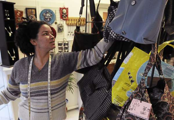Vicki Anderson aka The Dreaded Bag Lady hangs some of her bags created from used clothes at Maine Jewlery and Art in downtown Bangor on Wednesday, April 20, 2011.