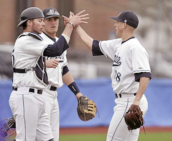 Maine pitcher Keith Bilodeau (38) gets congratulated by teammates catcher Fran Whitten and Justin Leisenheimer after winning game one of their Sunday doubleheader against Albany in Orono Sunday, April 24, 2011.