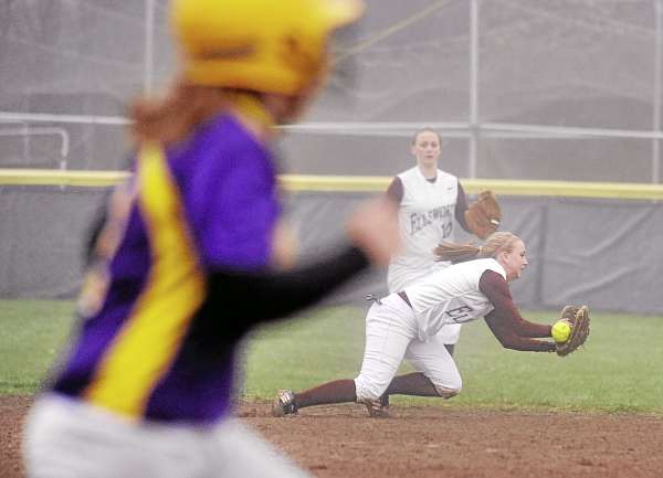 Bucksport High School's Jen Wight (left) runs to first base as Ellsworth High School's Sam McGuire dives but can't catch the ball during the third inning in Bucksport Thursday afternoon. The game ended after the top of the fifth inning with Bucksport winning 12-0.