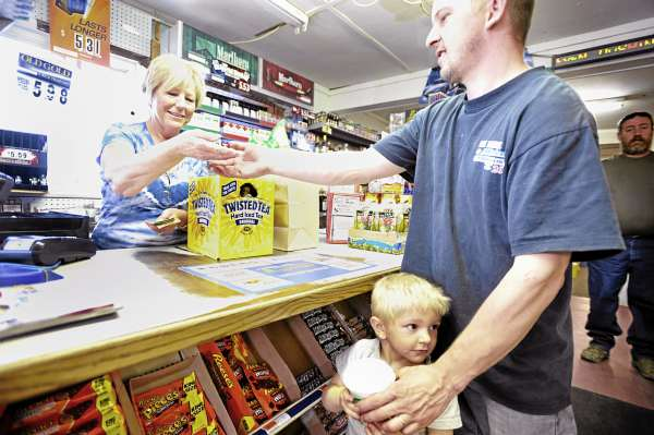 Barbara Collins, left, owner of Roger's Market in Hudson, makes change for customer Shannon Severance of Bradford while he shopped with his son Coby, 4, Friday morning April 29, 2011.The Collins family and scores of other Maine convenience store owners are wondering how the recent abrupt closure of distributor Associated Grocers of Maine will impact the product supply line to their stores.