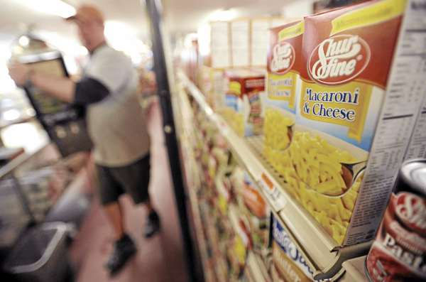 Lugging an oversize coffee maker, Roger Collins Jr. walks past a shelf of Shurfine macaroni and cheese boxes at Roger's Market in Hudson Friday morning April 29, 2011. The Shurfine products line was distributed by Associated Grocers of Maine until the Gardiner-based distributor closed this week. The Collins family and scores of other Maine convenience store owners are wondering how the recent abrupt closure of distributor Associate Grocers of Maine will impact the product supply line to their stores.