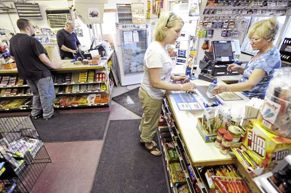 Barbara Collins, right, owner of Roger's Market in Hudson, rings up a purchase by customer Cindy MacDonald of Dover-Foxcroft as Collins' husband Roger Collins Sr. assists another customer Friday morning, April 29, 2011.The Collins family and scores of other Maine convenience store owners are wondering how the recent abrupt closure of distributor Associated Grocers of Maine will impact the product supply line to their stores.