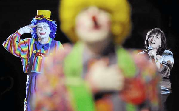 "NO CLOWNING AROUND: ""Fou"" (left) joined other Anah Shrine clowns in saluting the U.S. flag as Stephani Erb (right) of Brewer sang the Star Spangled Banner at the start of  the Anah Temple Shrine Circus' opening show a the Bangor Auditorium Friday, April 29, 2011. The annual circus runs Friday through Sunday."