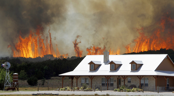 A wildfire threatens a house near Possum Kingdom, Texas, Tuesday.