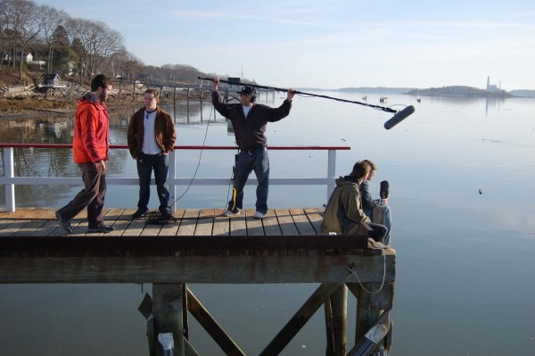 "Lead actor Matthew Pennington and director Nicholas Brennan discuss a scene during production on the short film ""A Marine's Guide to Fishing"" at Handy Boat Services in Falmouth, while crew members (L-R Brendan Barry, Jesse Magur and Jeffrey Ryan Kelsey) get ready for the shot."