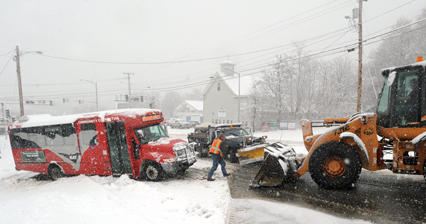 Brewer Public Works employee Gordon Tarent (center)hooks a chain to a front-end-loader preparing to pull a BAT bus back onto State Street after it slipped sideways off the icy roadway.