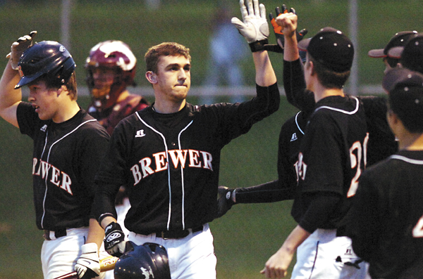 Billy Bissell of Brewer (center), is congratulated by his teammates after hitting a two-run home run in a Class A baseball victory over Bangor at Heddericg Field in Brewer in 2009.