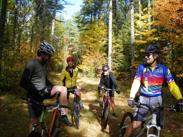 Rose Bike Shop owner Jim Rose, right, and riding companions (from left) Matt Cote, Karl Johnson and Bob Lombardo, all of Orono, take a break from riding the woods trails in Orono.