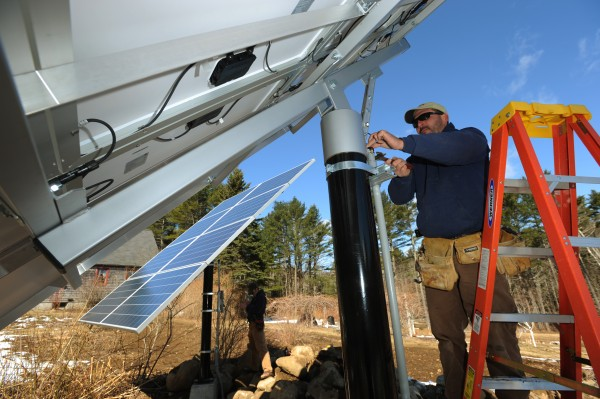 ReVision Energy employee Brian Bryne (right) and Eric Herz (left) finish up wiring on a pair of solar collectors on a Camden home on Wednesday, April 6, 2011.