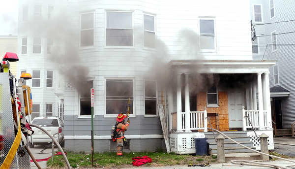 A Lewiston firefighter breaks out windows in a first-floor apartment at 153 Bartlett Street on Sunday afternoon as they battled a blaze inside. The fire was knocked out quickly.