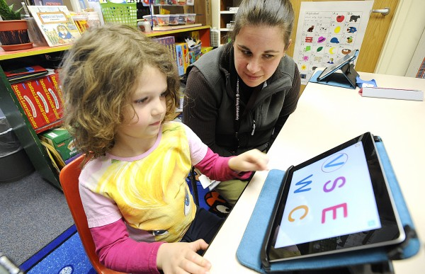 Rhianah Landry, 5, a kindergarten student at Washburn Elementary School in Auburn, works with literacy instructor Mauri Dufour on a borrowed Apple iPad 2 tablet computer Thursday. Educators were excited about a School Committee decision Wednesday to give all Auburn kindergarten students iPad 2 tablets in the fall. Rhianah used the notebook to hear a story and to learn her letters.